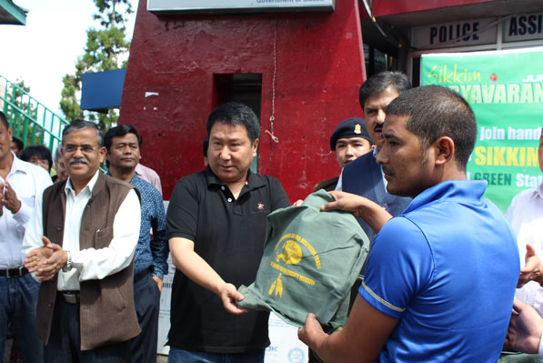 Honourable Minister Forests Shri T W Lepcha handing garbage disposal bags for vehicles to taxi drive
