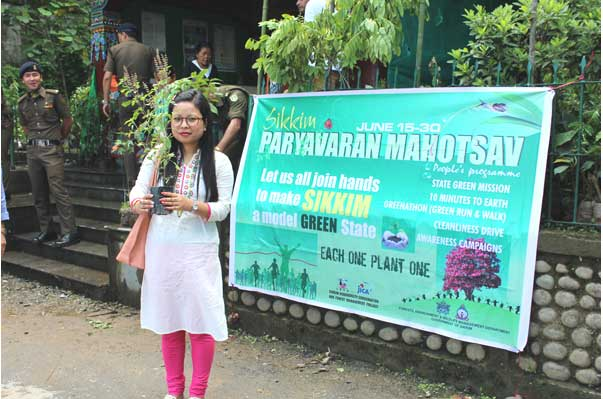 A young girl with a sapling amidst forest officials at seedling distribution booth at Zero Point Gan
